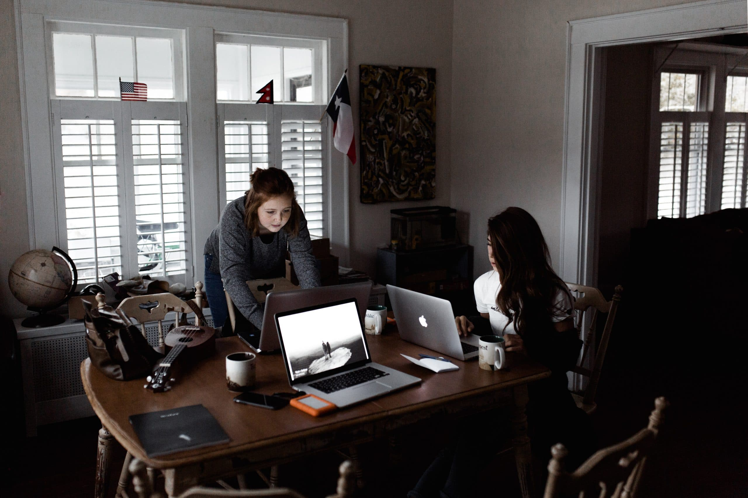Two women working on their laptops at a table