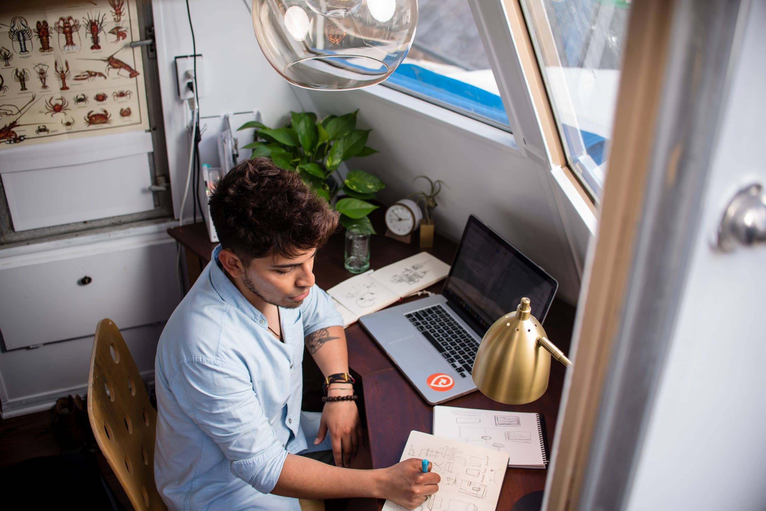 A live chat agents working from home sits at a desk in front of a window taking notes.