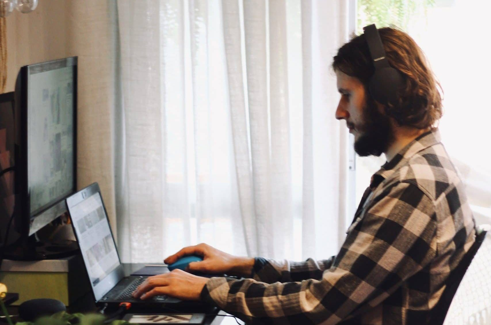 A work from home contact center agent in a plaid shirt sits at a desk in front of a computer wearing a headset.