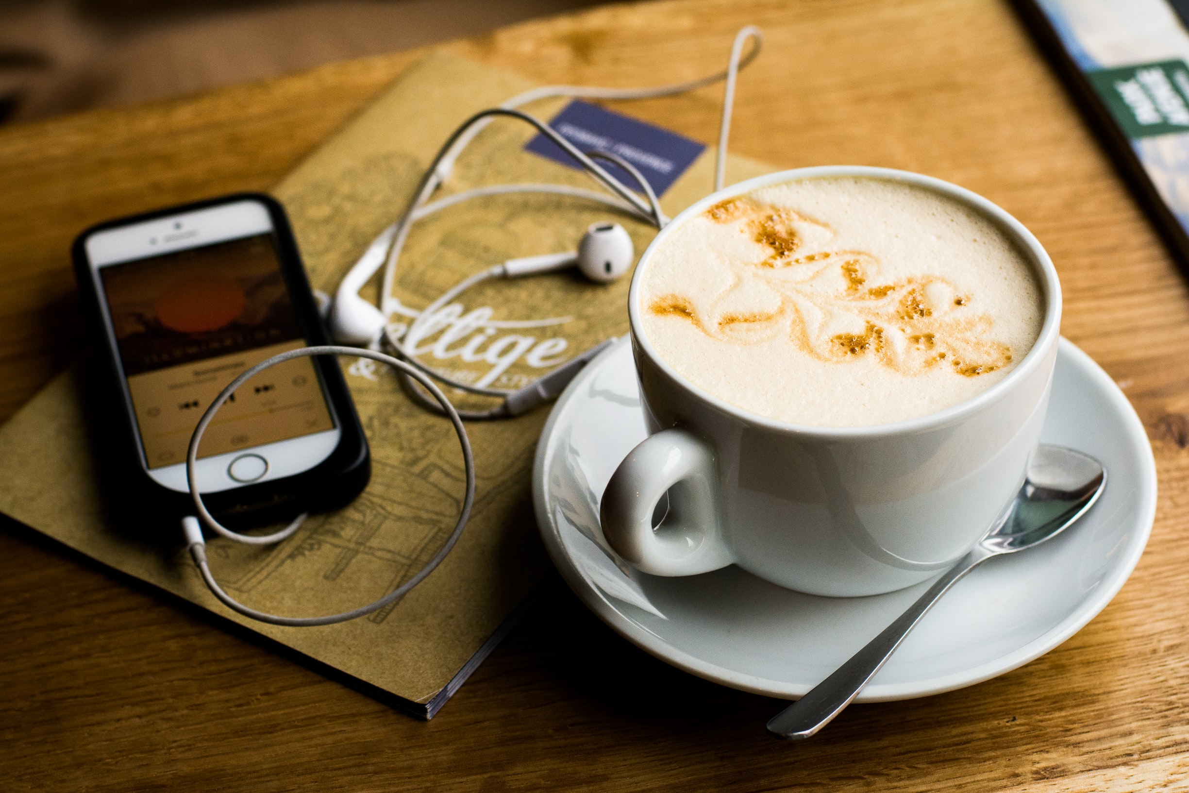 A phone playing a customer experience podcast sits on a table next to a cup of coffee